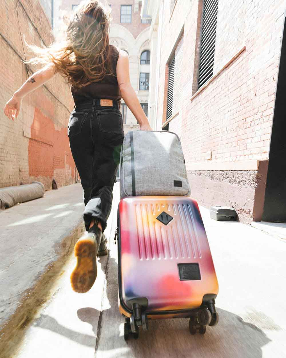 A woman is running down a side street pulling her Trade Luggage Carry-On Large in Windsor Wine/Orange Gradient with a Raven Crosshatch Travel Backpack on top.