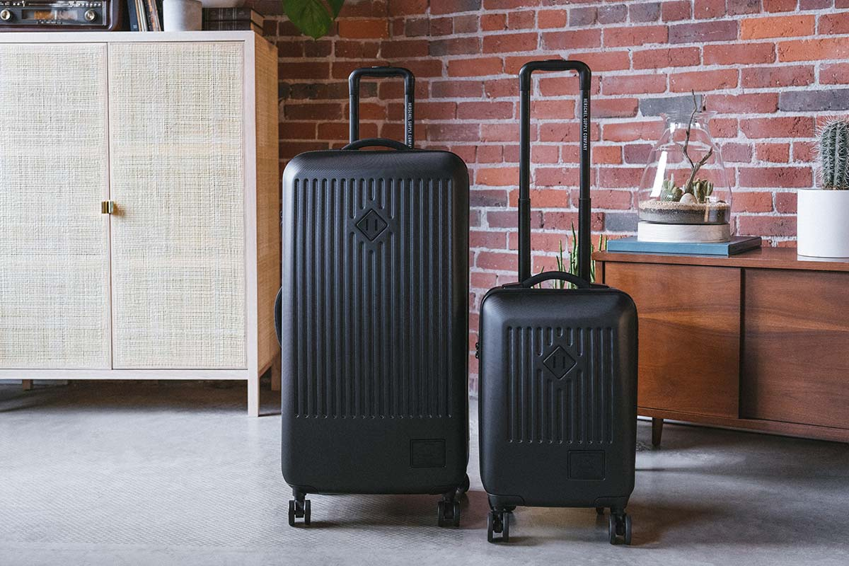 A black Trade Luggage Large & Trade Luggage Carry-On next to each other in an exposed brick apartment