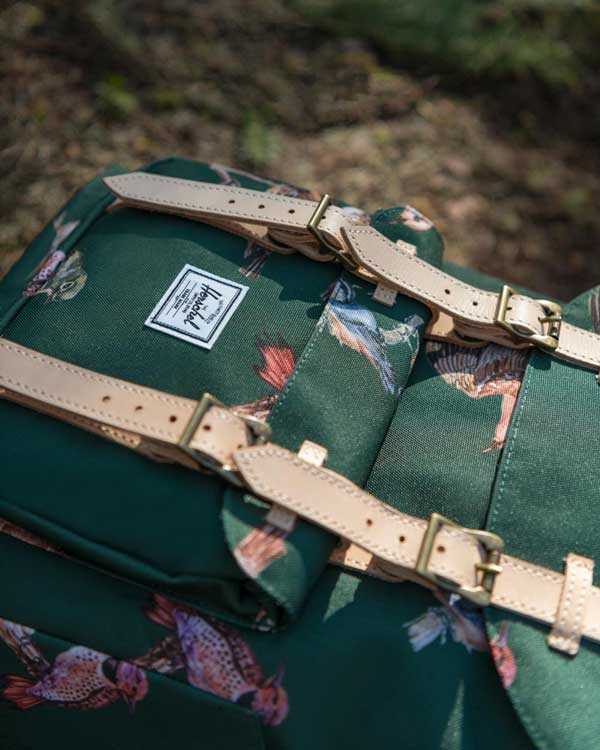 A Herschel Little America Backpack from the birds of herschel collection sitting on the ground